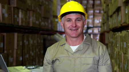 работник физического труда : Warehouse worker smiling at camera in a large warehouse