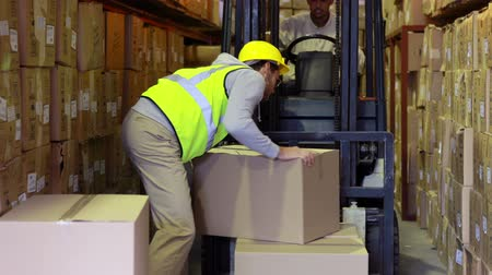 karton : Warehouse worker packing boxes on forklift in a large warehouse
