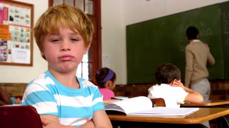 unott : Bored little boy blowing through lips during class in slow motion Stock mozgókép