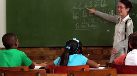 öğretim : Young teacher teaching math to young class in classroom in slow motion