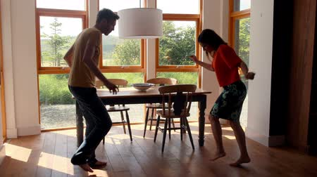 ostoba : Cute young couple dancing together at home in kitchen