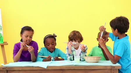 preschool : Cute pupils painting eggs for easter at the elementary school Stock Footage