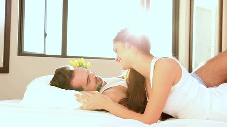объятие : Attractive couple lying in bed in the morning at home in bedroom Стоковые видеозаписи