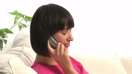 kanapa : Stock footage of a Woman alone on a Sofa talking on the phone Wideo