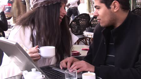 somente para adultos : Two young adults working on a laptop in a cafe
