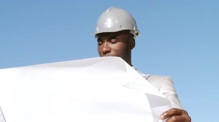 corporate affairs : Responsible architect looking on a blueprint plan thinking implementing a buildingplan