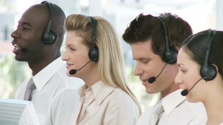 asistan : Team of people talkin on headsets in call centre