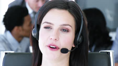 merkez : Footage of portrait of businesswoman talking on a headset in a call center with her team working in the background