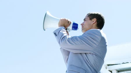 мегафон : Footage of young businessman shouting into a megaphone outdoors with blue sky in the background