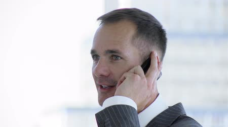 arc : Smiling businessman talking on mobile phone in office footage in high definition Stock mozgókép