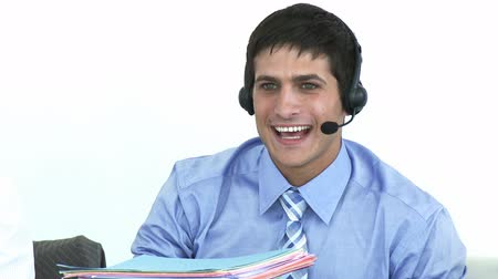 hívó : Footage of smiling businessman talking on a headset in a call center in high definition
