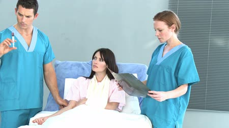 seringa : Male doctor giving an injection to a beatiful female patient recovering in bed while a female doctor is examining an x-ray. Footage in high definition. Concept of healthcare Stock Footage