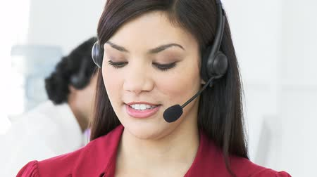 képviselő : Close-up of beautiful woman working in a call center with a headset on. Footage in high definition