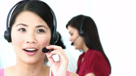 телемаркетинг : Close-up of Asian woman working in a call center with a headset on. Footage in high definition Стоковые видеозаписи