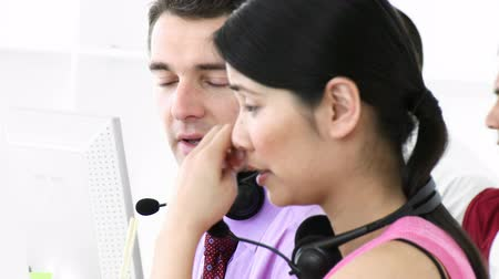 fejhallgató : Footage of man and woman speaking with each other in a call center in high definition