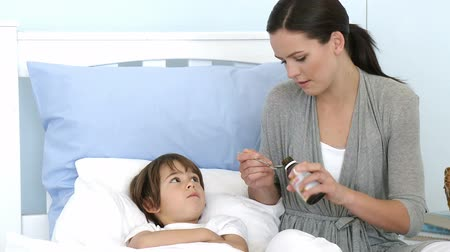 ilaçlar : Mother giving her son cough medicine because of the flu. Footage in high definition. Concept of healthcare