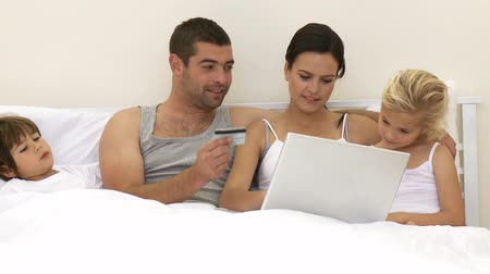 nákupy : Family in bed buying online with a laptop. Footage in high definition