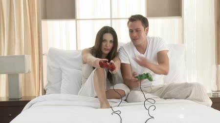 дичь : Happy husband and wife playing videogames in bed. Footage in high definition