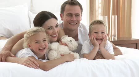 lefekvés : Smiling young family lying in bed together. Footage in high definition Stock mozgókép