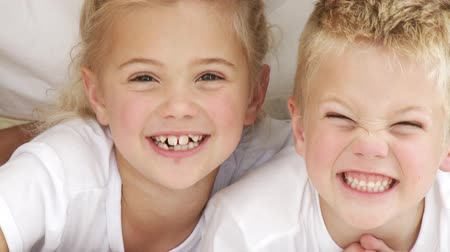 hozzábújva : Close-up of smiling sister and brother in bed. Footage in high definition
