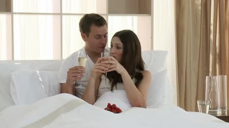 valentin nap : Happy young lovers drinking champagne in bed. Footage in high definition