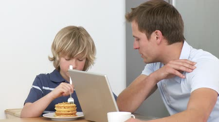 kahvaltı : Footage in high definition of father using a laptop and son eating a sweet in the kitchen