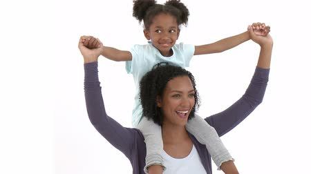 afro americana : Ethnic mother giving her daughter piggyback ride against black background. Footage in high definition Stock Footage