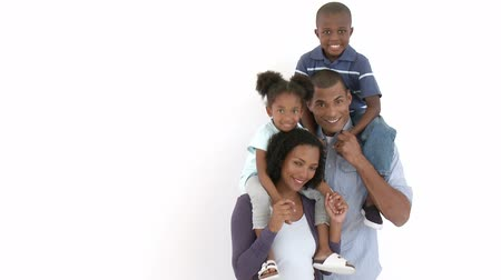 portre : Afro-American parents giving their children piggyback rides against white background. Footage in high definition