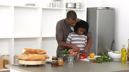 afro americana : Panorama of Afro-American father and son cutting vegetables in the kitchen. Footage in high definition