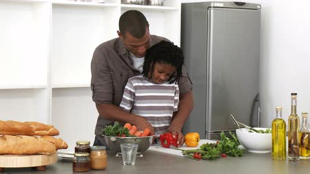 doğrama : Afro-American father and son cutting vegetables in the kitchen. Footage in high definition Stok Video