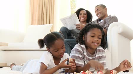 afro amerikai : Footage in high definition of Afro-American siblings playing with cube toys in the living-room with their parents sitting on the sofa at home Stock mozgókép