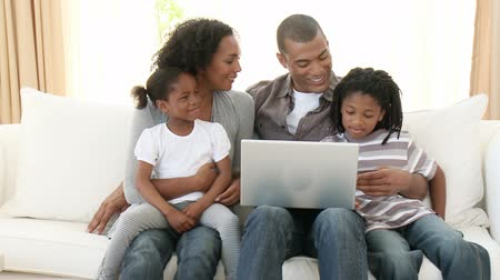 afro americana : Panorama of Afro-American family using a laptop on the sofa. Computer generation. Footage in high definition