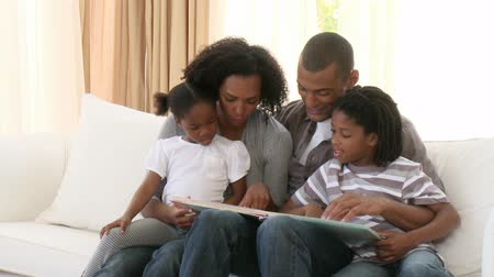 ler : Footage in high definition of Afro-American parents and children reading a book in the living-room