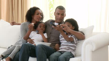 afro americana : Footage in high definition of Afro-American parents and children watching television in the living-room
