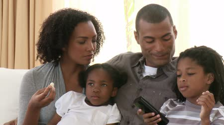 afro americana : Close-up of Afro-American parents and children watching television at home. Footage in high definition Stock Footage