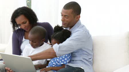 afro americana : Panorama of Afro-American family using a laptop on the sofa. Footage in high definition