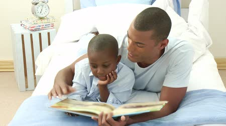öğretim : Afro-American little boy reading a book with his father in bed. Footage in high definition