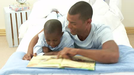 elszigetelt fekete : Footage in high definition of Afro-American little boy and his father reading a book in bedroom