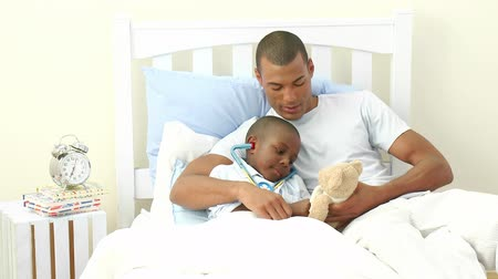 afro americana : Footage in high definition of Afro-American father and sick son playing doctors in bed
