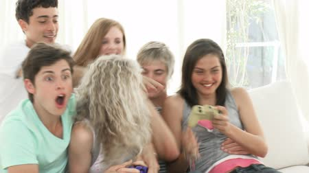 oynamak : Panorama of teenagers having fun playing video games at home. Footage in high definition