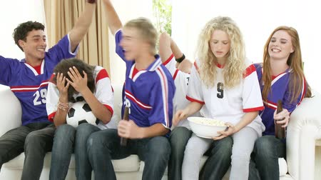 pré adolescente : Footage in high definition of a group of excited and happy teenagers watching a football match at home