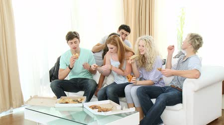 elvihető : Footage in high definition of happy adolescents eating pizza at home