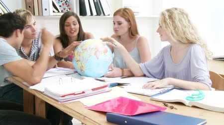 земной : Teenagers in a library working with a terrestrial globe and taking notes. Footage in high definition Стоковые видеозаписи