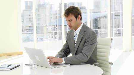 male : Serious businessman working at a laptop in his office Stock Footage