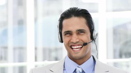 fejhallgató : Selfassured businessman using a headset in a company Stock mozgókép