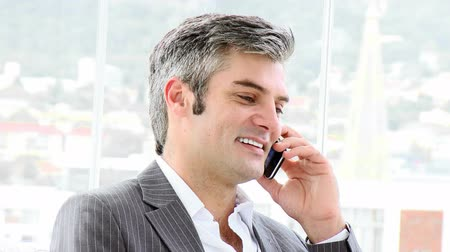 mluvení : Mature businessman calling by phone in a company