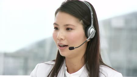 clientes : Asian customer agent with headset on in her office
