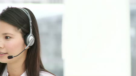 fejhallgató : Attractive businesswoman with headset on in the office Stock mozgókép