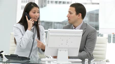 employee : Assertive business team working at a computer in a company