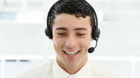 képviselő : Smiling businessman with headset on in a company